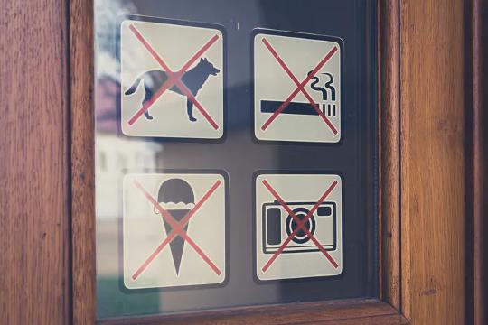Teken op 'n deur wat nie toegang tot honde weier nie. Ook nie rook nie, geen kameras en geen roomys nie.