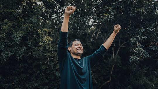 hombre con los brazos levantados en el aire en señal de triunfo