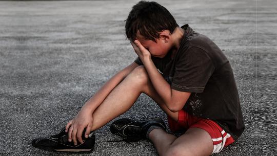 男孩坐在人行道上抱著他的腳踝和他的頭...似乎很痛苦