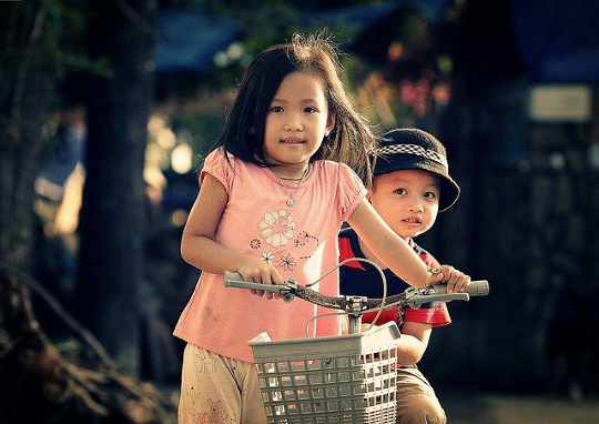 niña en una bicicleta con su hermano sentado detrás de ella