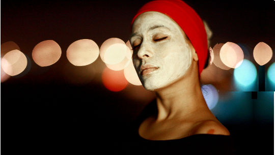 kvinne iført turban og med en gjørme eller leiremaske i ansiktet