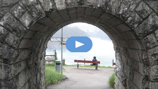 왼쪽 또는 오른쪽을 가리키는 표지판이있는 터널 끝의 벤치에 앉아있는 사람
