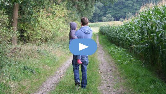 far som holder sønn i armene og går nedover veien