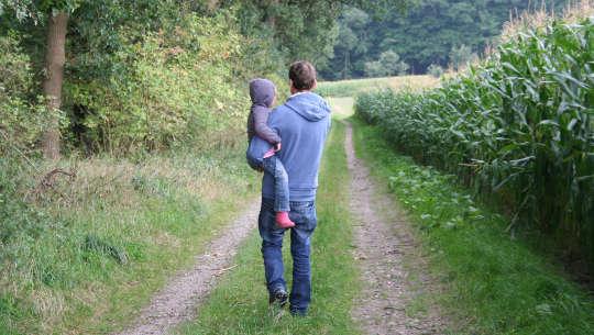 isä, joka pitää poikaa sylissään ja kävelee tietä pitkin