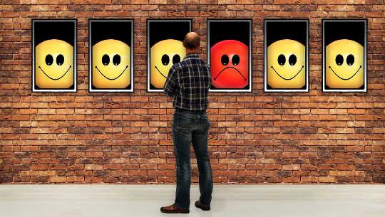 用笑臉和一張非笑臉看著窗戶的男人
