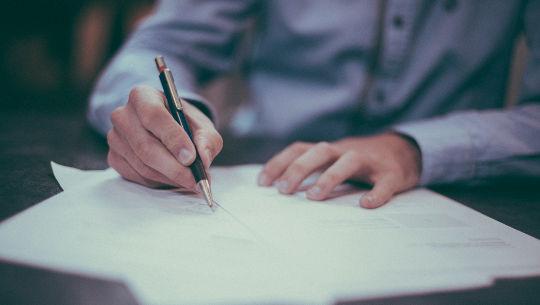 आदमी बैठकर लिख रहा है