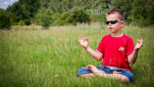 Jeune garçon portant des lunettes de soleil méditant dans un champ ouvert