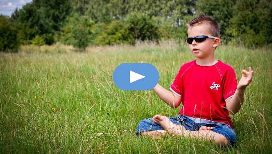 खुले मैदान में ध्यान करते धूप का चश्मा पहने छोटा लड़का