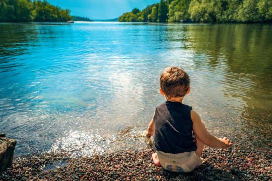 jong kind zit aan de rand van een vredig meer