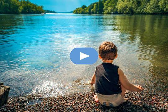 शांत झील के किनारे बैठा छोटा बच्चा