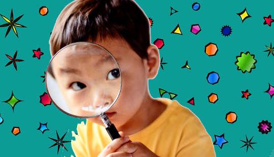 Kind schaut durch eine Lupe