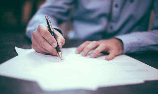 bild av en man som skriver på pappersark