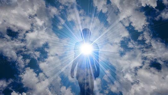 person som utstrålar kärlek och ljus från sitt hjärta ut i universum