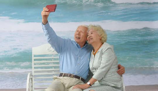 plus vieux couple aux cheveux blancs assis sur un banc à la plage en prenant un selfie