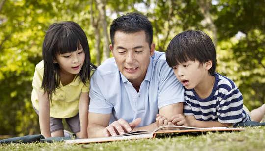 เด็กสองคนอ่านหนังสือกับพ่อ