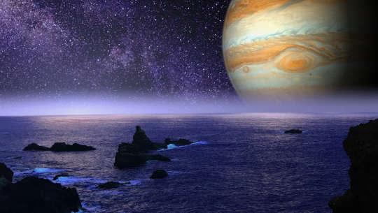image de la planète Jupiter sur l'horizon d'un rivage rocheux de l'océan