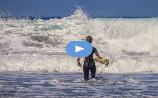 surfare med liten surfbräda inför enorma vågor