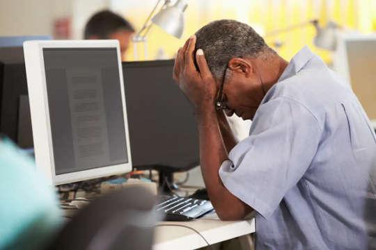 גבר מחזיק ראש בידו מול מסך מחשב