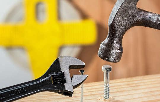 en hammare som försöker slå i en bult och en skiftnyckel som försöker arbeta med en spik