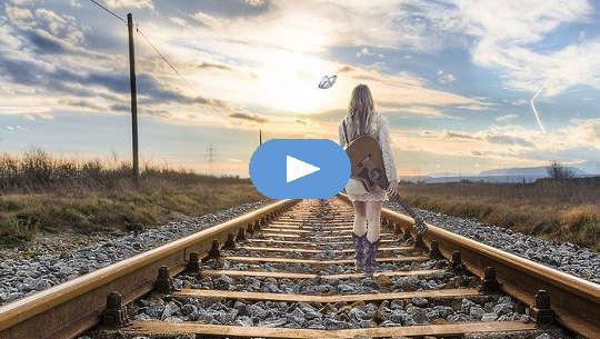 Flicka med en gitarr på ryggen som går nerför järnvägsspåren.