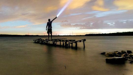 गोदी पर खड़ा आदमी आसमान में टॉर्च चमका रहा है