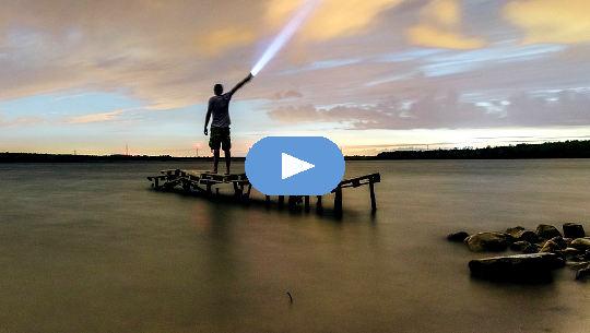 mies seisoo laiturilla ja paistaa taskulampun taivaalle