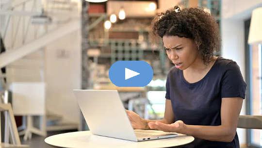 järkyttynyt nainen istuu avoimen kannettavan tietokoneensa edessä