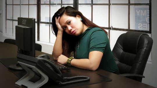 Frau sitzt an ihrem Schreibtisch und sieht besorgt aus