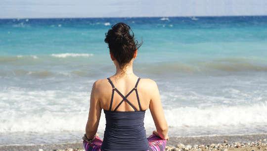 vy från baksidan av en kvinna som sitter på stranden i meditation
