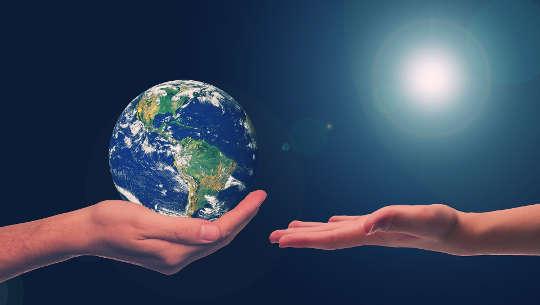 två händer, en håller jorden, den andra handen öppen för att ta emot