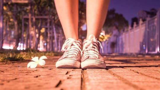två fot i sneakers vända framåt