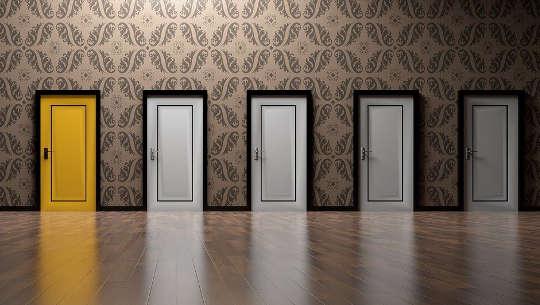 fünf geschlossene Türen, eine gelb lackiert, die anderen weiß