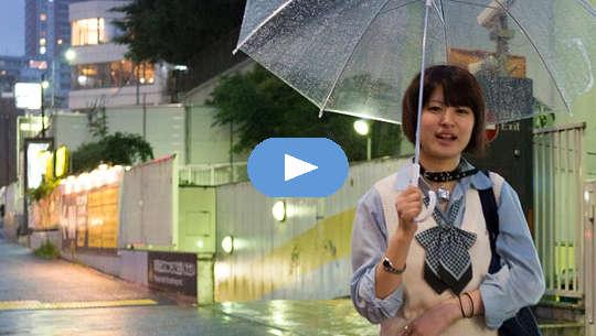 Jovem sorridente caminhando com o guarda-chuva aberto
