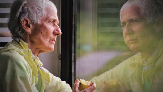 người lớn tuổi đang ăn táo và nhìn vào hình ảnh phản chiếu của cô ấy trong cửa sổ