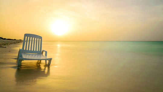 Μια καρέκλα εν μέρει στο νερό σε μια αμμώδη παραλία