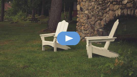دو صندلی چمن خالی از دیوار سنگی