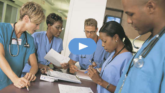 grupa pracowników służby zdrowia stojących wokół biurka lub stołu