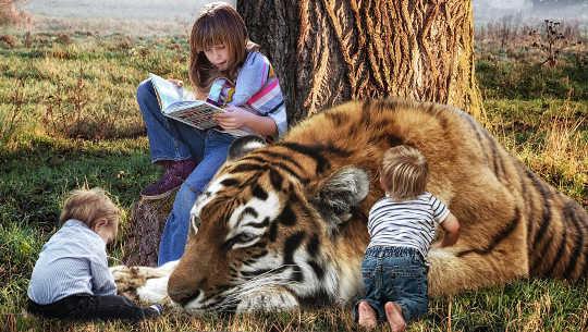 młoda dziewczyna czytająca książkę i siedząca obok tygrysa i dwójki bardzo małych dzieci