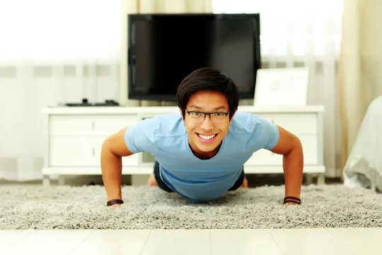 Glimlachende man doet pushups thuis