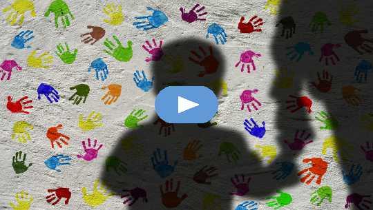 silhouet van een jongen die de hand van een volwassene vasthoudt, met een achtergrond van kleurrijke handafdrukken op de muur