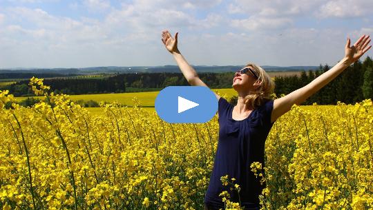 Mujer de pie en un campo de flores con los brazos extendidos hacia el sol