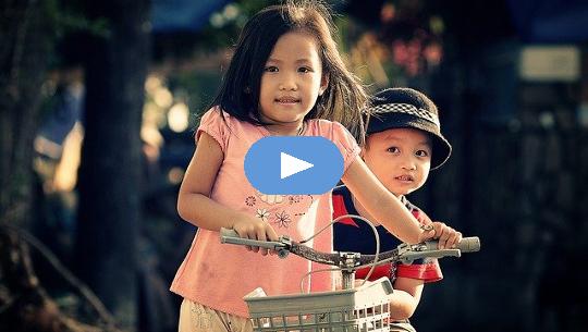 ung flicka på cykel som bär sin unga bror bakom sig