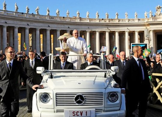 교황은 열려있는 차에서 타고있다.
