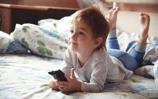 छोटा लड़का बिस्तर पर टीवी देख रहा है