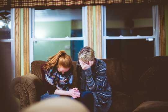 Två kvinnor sitter på en soffa och verkar nödställda.