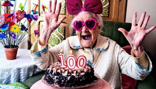 En kvinne ser spent ut med rosa briller og bue på, ser på en kake med