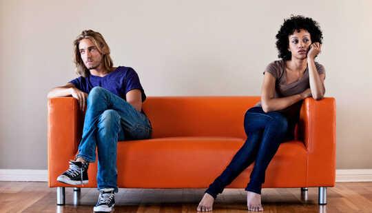 Bir çift turuncu bir kanepenin karşı taraflarında oturuyor ve birbirinden uzağa bakıyor.