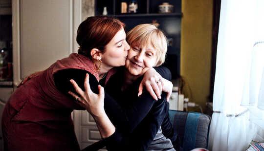 En yngre kvinne klemmer moren sin