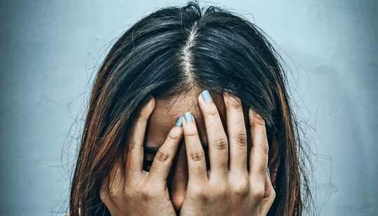 Uma mulher cobre o rosto com as mãos