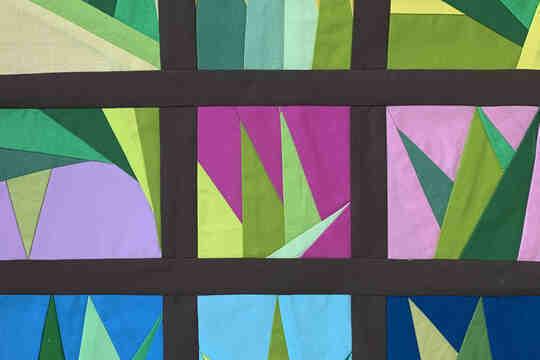 Một mô hình chần bông với một số hình tam giác màu xanh lá cây trong các tấm hình vuông khác nhau